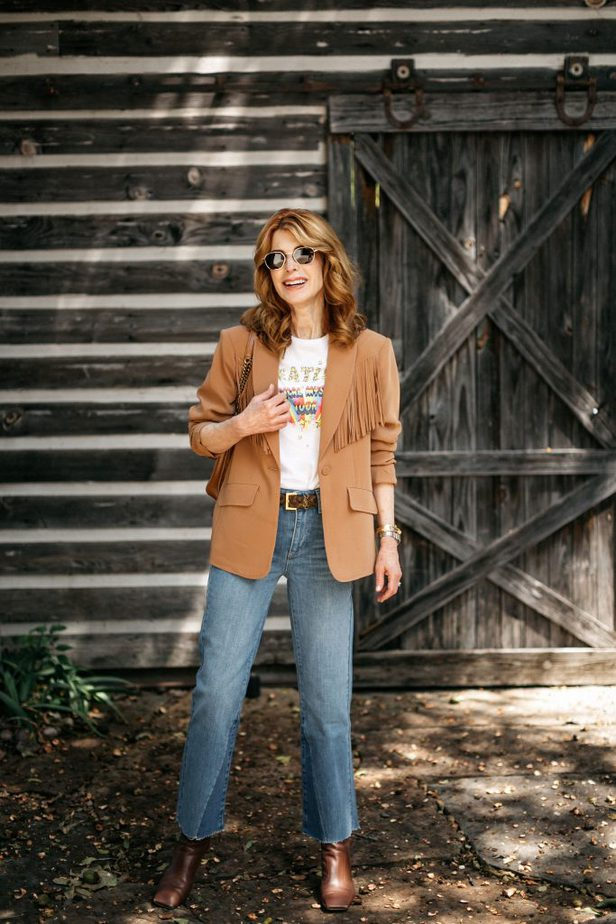 woman posing and wearing shirt, fringe blazer, and jeans