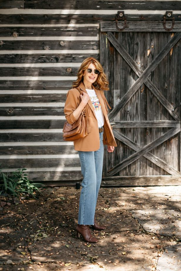 woman holding bag and wearing shirt, fringe blazer, and jeans