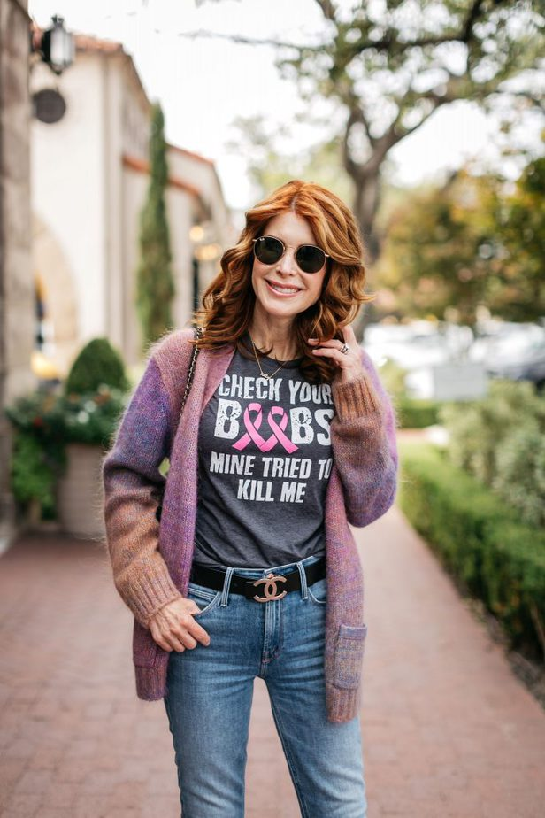 woman wearing breast cancer shirt and jeans