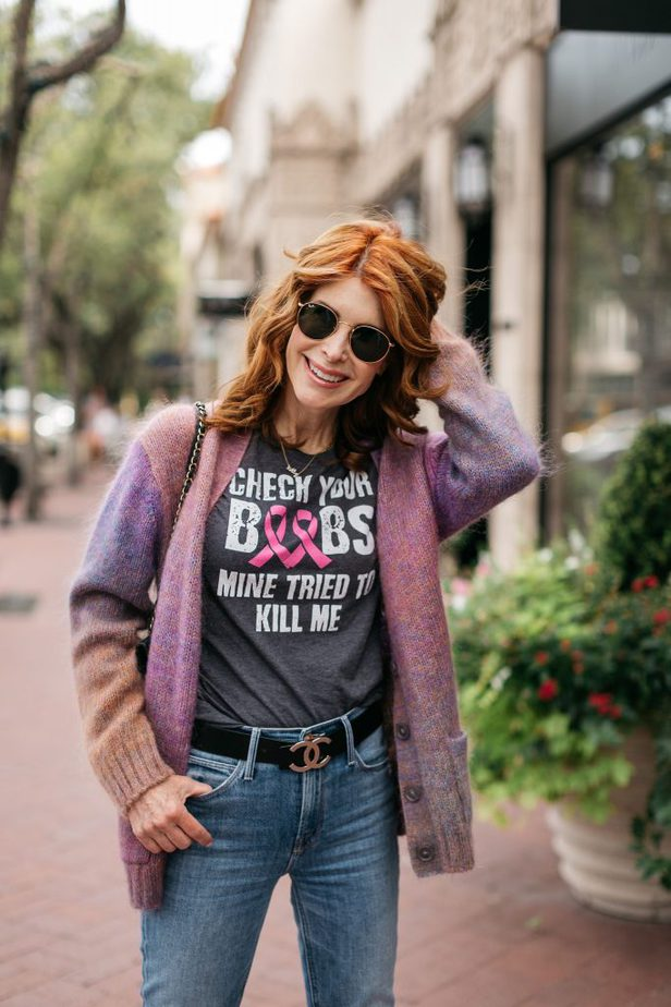 woman wearing breast cancer shirt, sweater and jeans