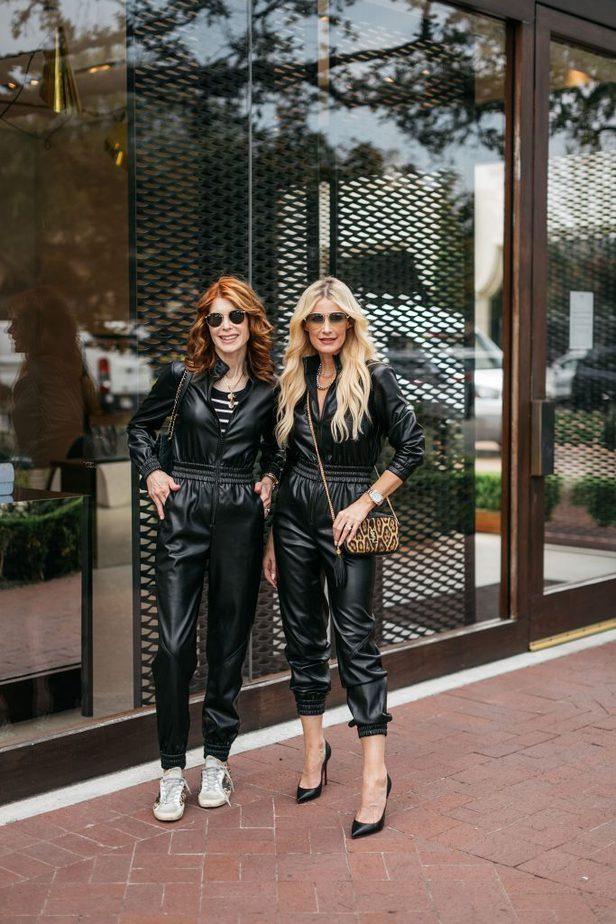 two women wearing faux leather jumpsuit