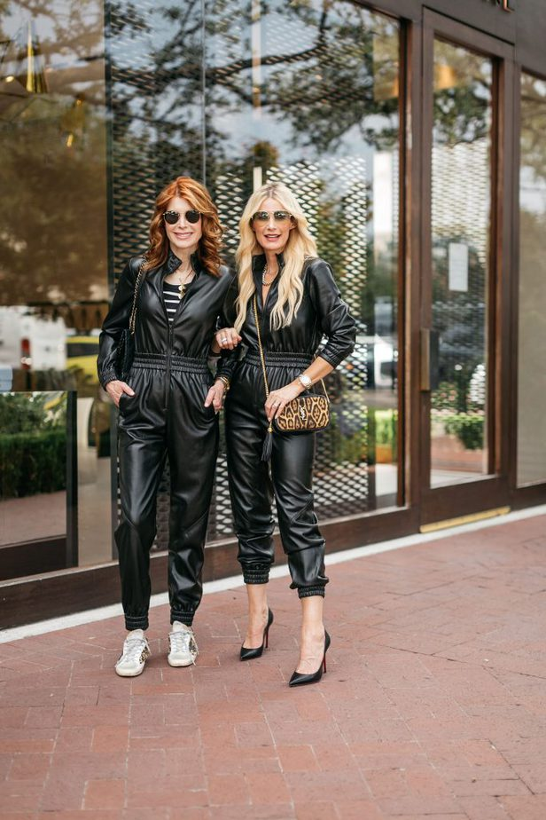two women wearing faux leather jumpsuit with hand bags