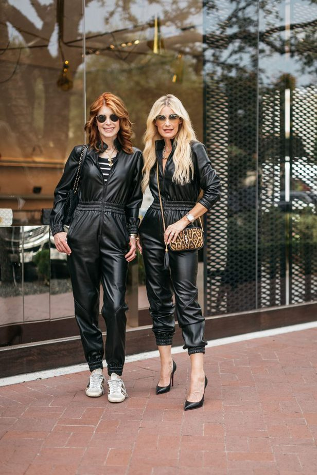 two women outdoors and wearing faux leather jumpsuit